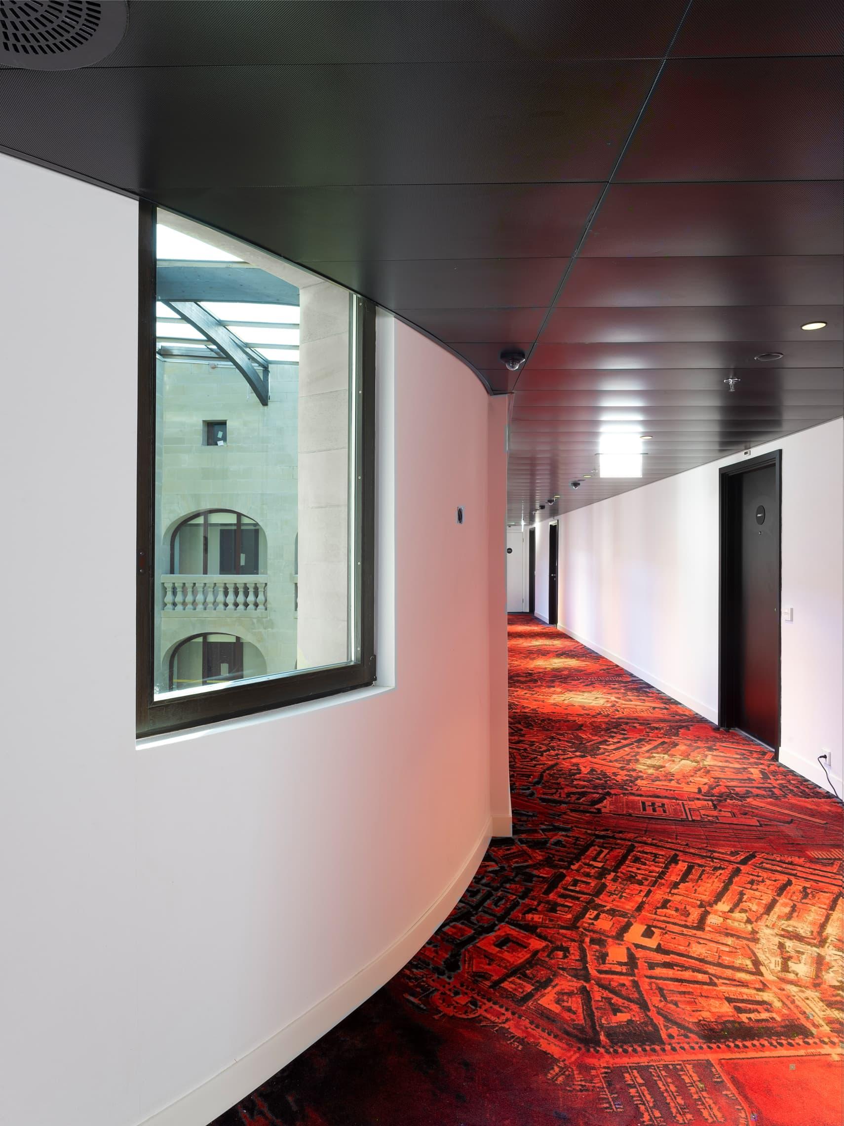 corridor d'hôtel avec une moquette qui représene le plan de la ville de Genève