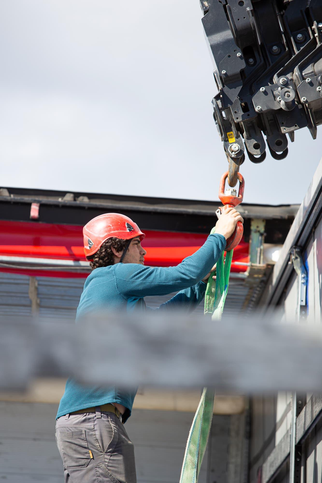 ouvrier en train de suspendre un câble