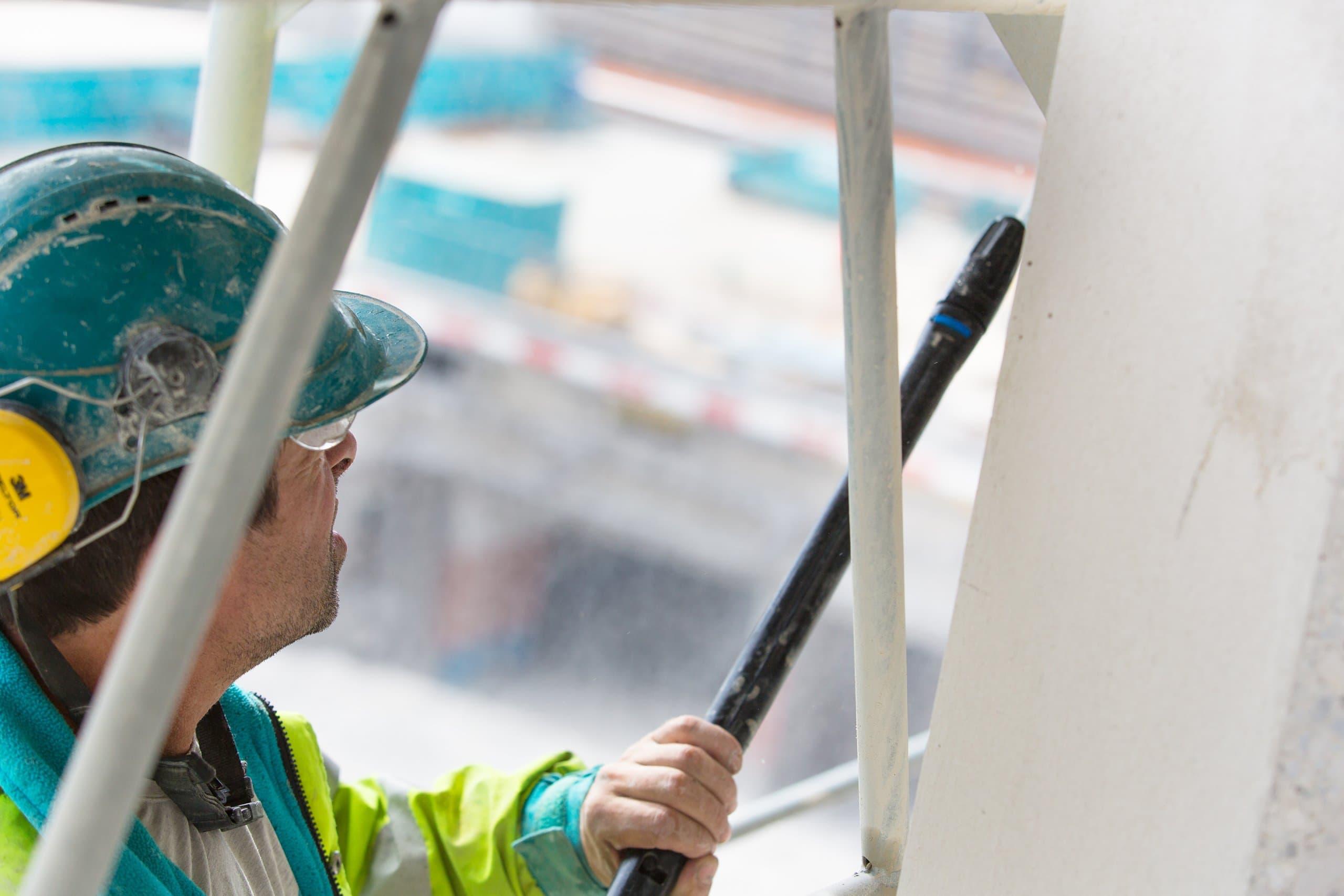 ouvrier de chantier en train de manier une lance à haute pression