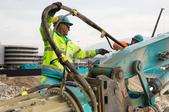ouvrier de chantier portant un tuyau