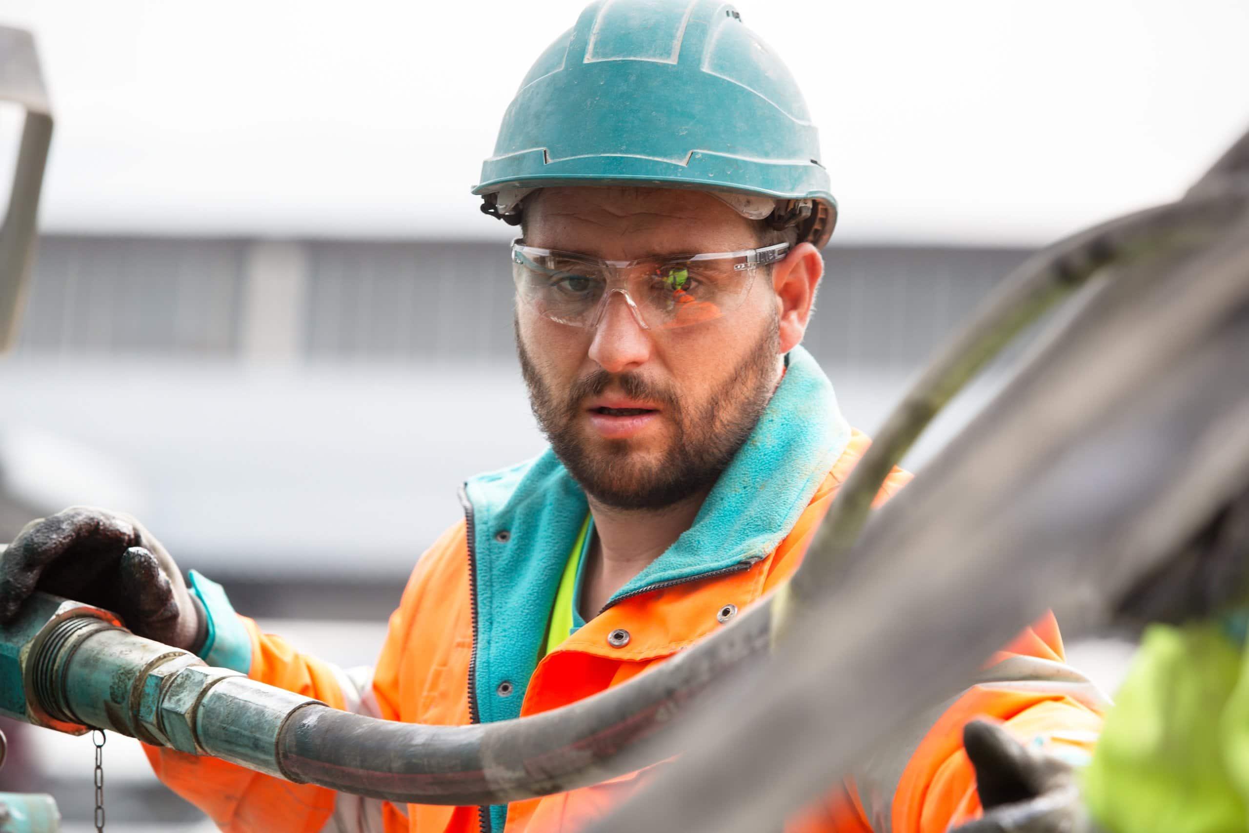 ouvrier avec casque de chantier qui tend le bras