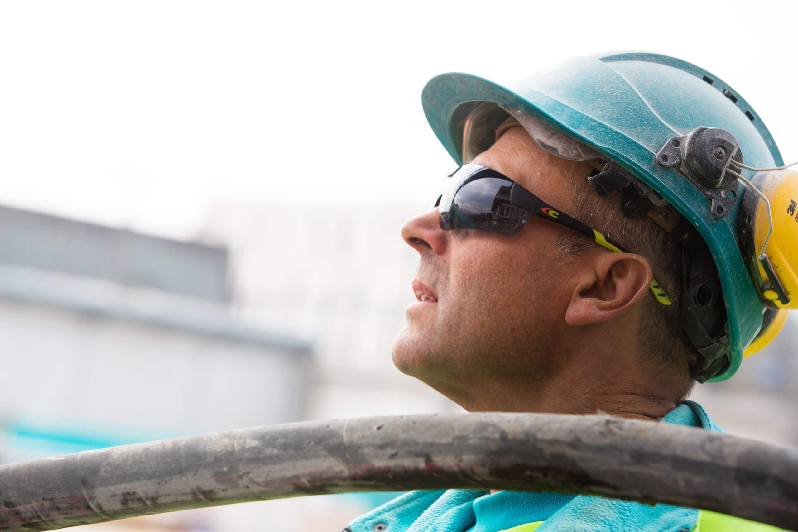 ouvrier avec des lunettes de chantier en train de regarder en l'air