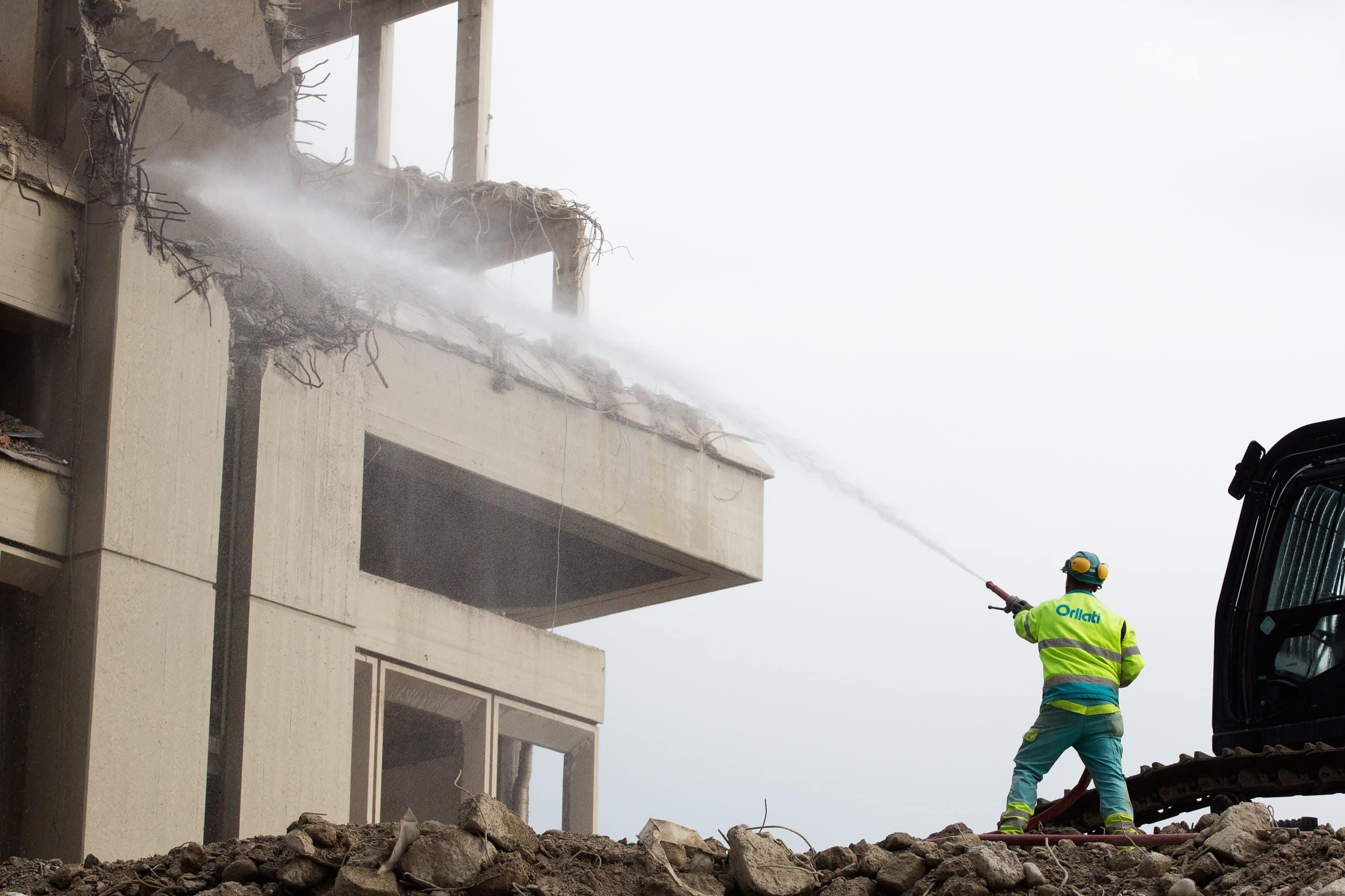 ouvrier de chantier maniant une lance à eau