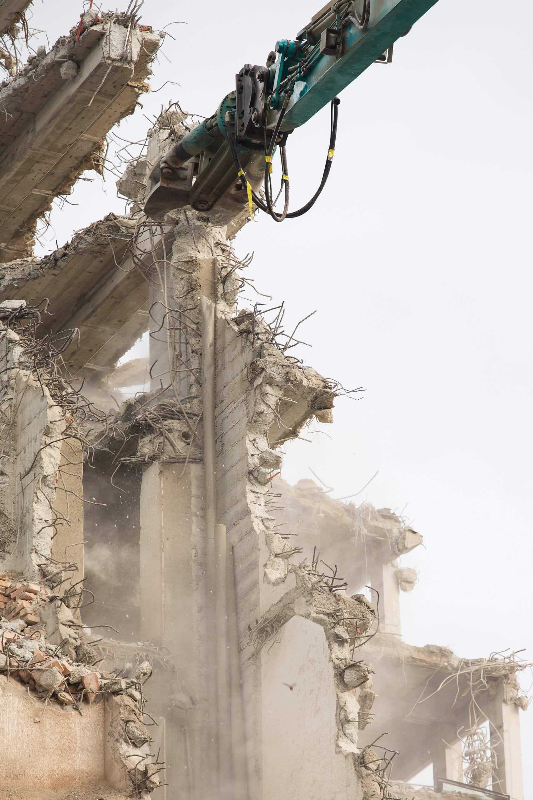 autre vue d'une pelle mécanique en train de détruire un immeuble