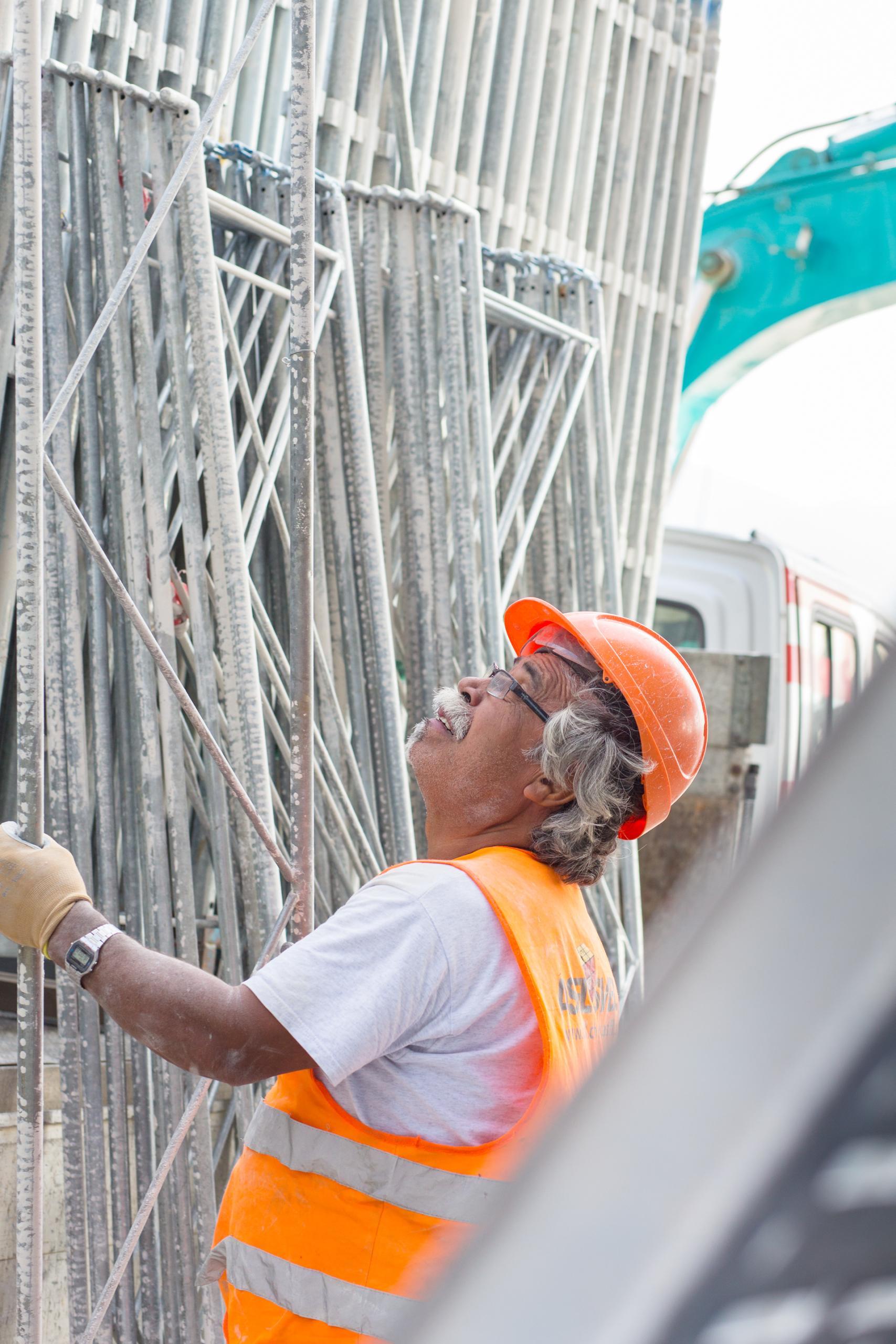 ouvrier de chantier en train de saisir des échafaudages