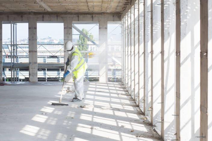 ouvrier de chantier en train de balayer sur un étage