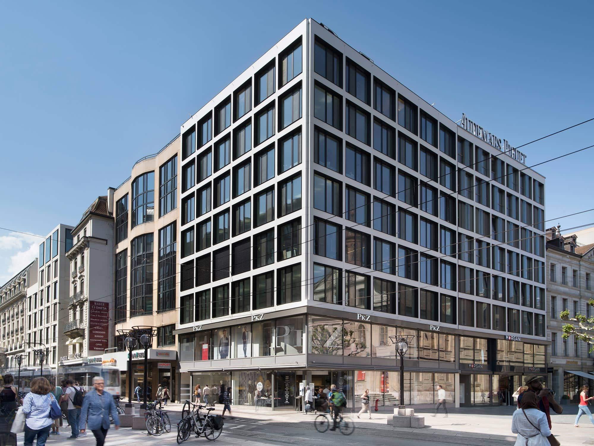 architecture à Genève montrant un angle de bâtiment avec façades adjacentes et stores levés