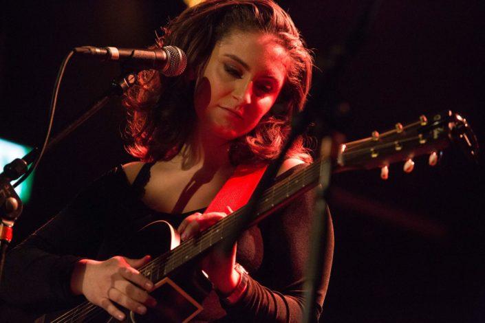 la chanteuse Submaryne qui regarde tendrement sa guitare