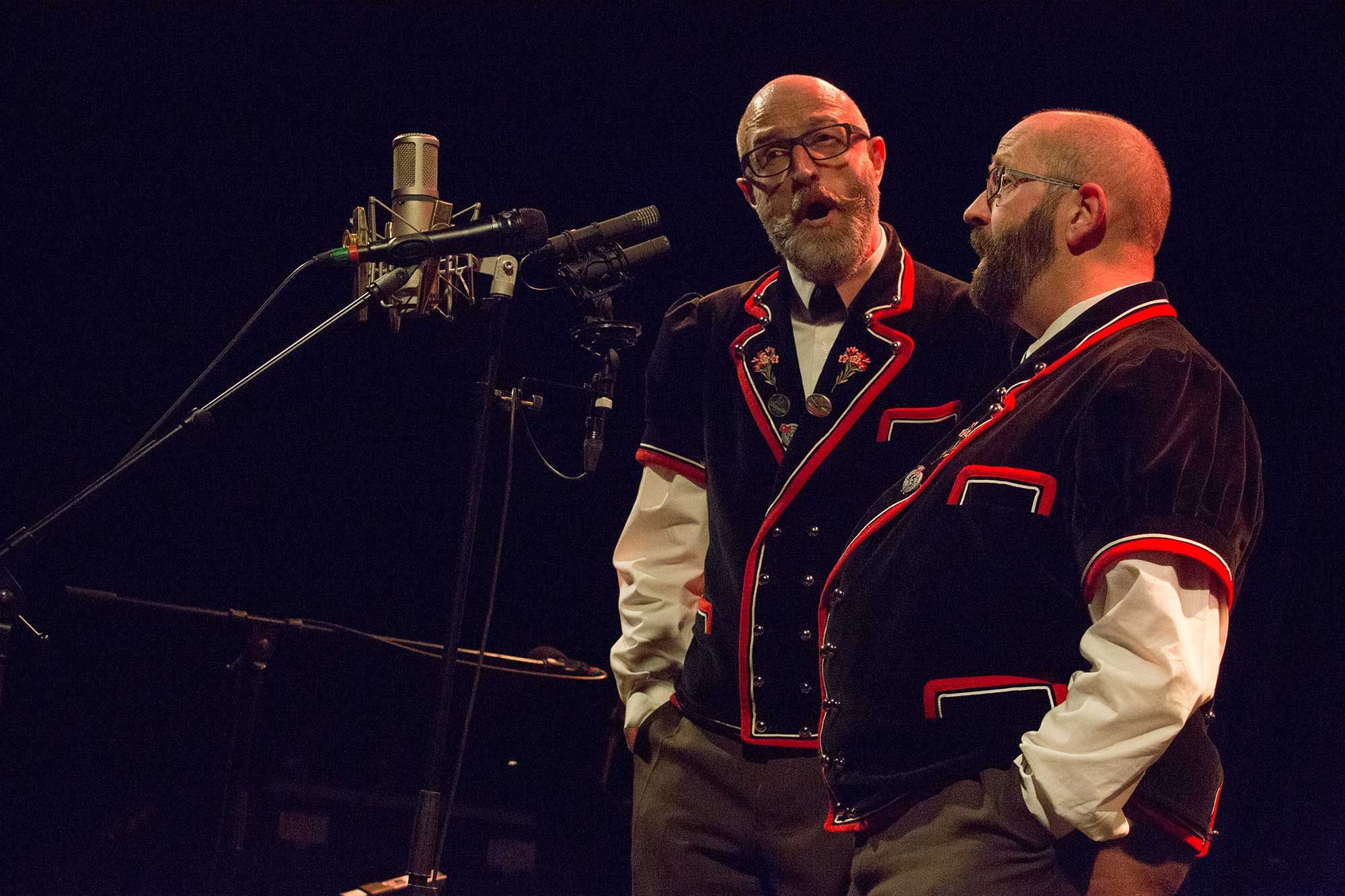 deux chanteurs en habits traditionnels la bouche ouverte