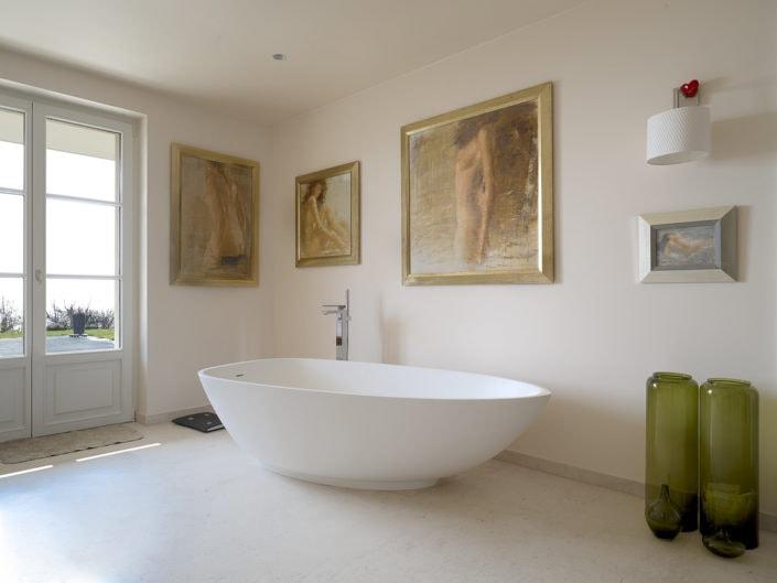 intérieur montrant une baignoire surmontée de tableaux de maître