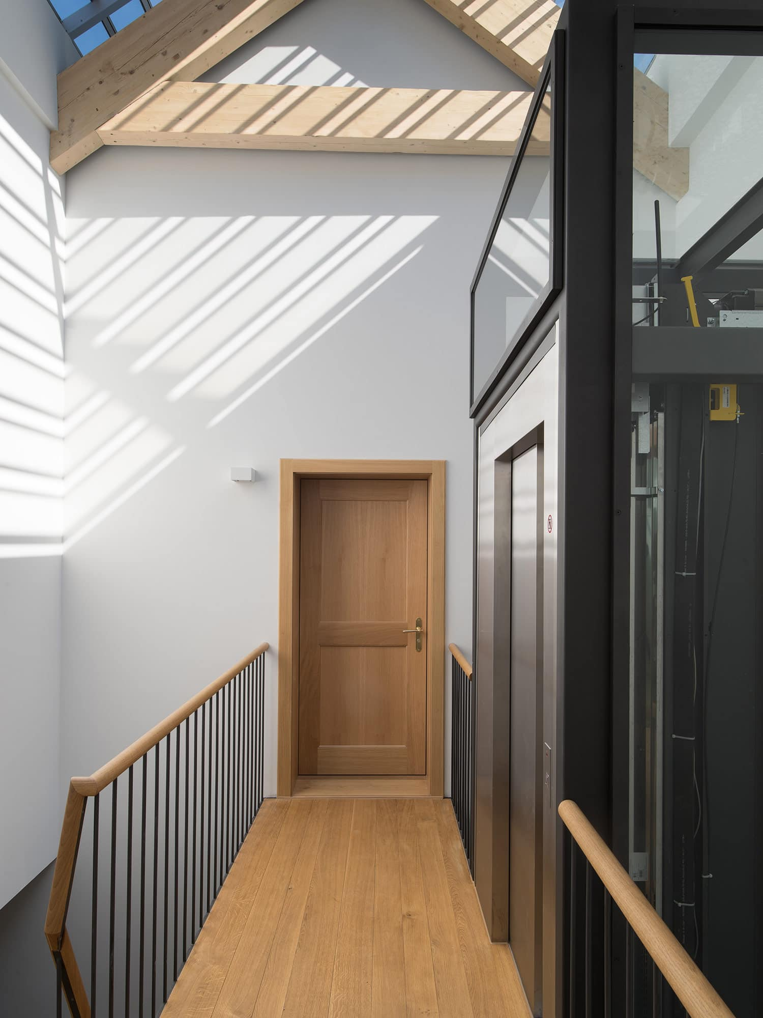 passerelle menant à une porte d'entrée et à un ascenseur imaginé par un bureau d'architectes à Lausanne